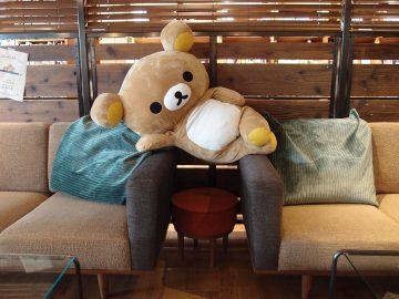 椅子と椅子の間に寝そべるリラックマ