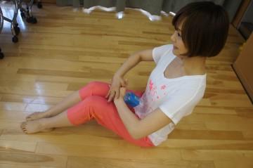 床に座り、膝を立てた状態でペットボトルをお腹にあてる