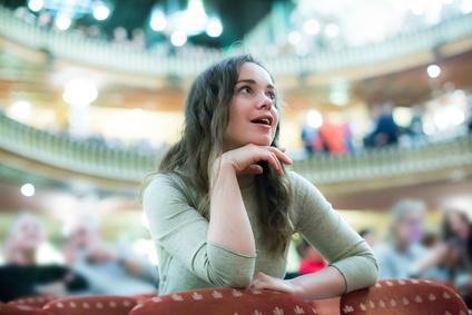劇場で舞台を見る女性