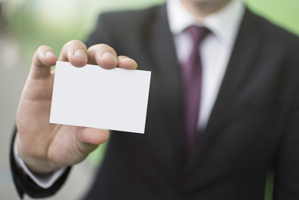 Close-up of a businessman's hand holding a business card. Blank business card. Copy space on a business card.