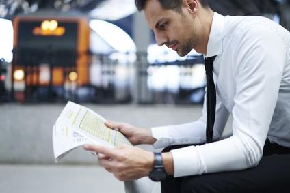 駅で新聞を読む男性