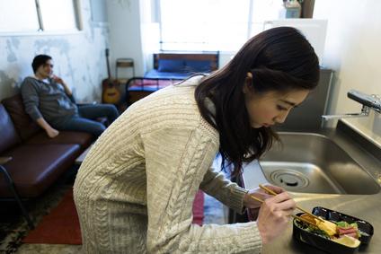 お弁当を作る女性と見守る男性