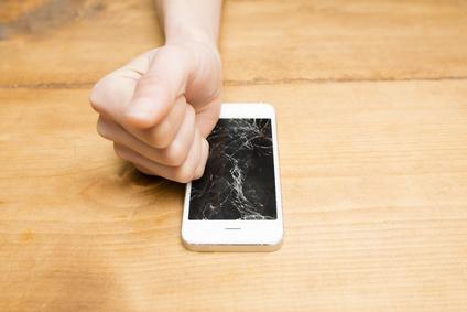画面がひび割れたスマートフォンと女性の手