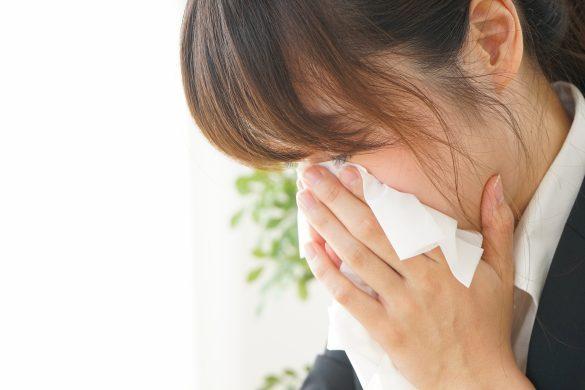 ティッシュで鼻をかむ若い女性
