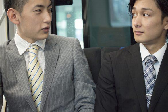 電車で会話する男性2人組