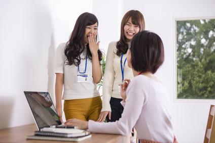 部屋でパソコンをする女性たち、職場いじめ、同僚