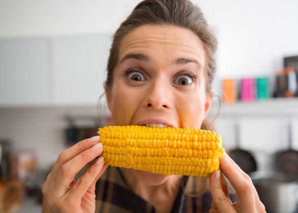 トウモロコシにかぶりつく女性