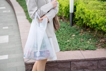 プラスチックレジ袋を持つ女性
