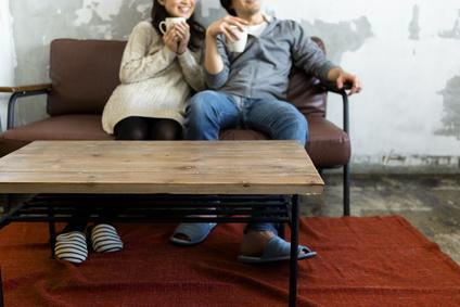 テレビを見ながらコーヒーを飲む若い夫婦、同棲カップル、おうちデート