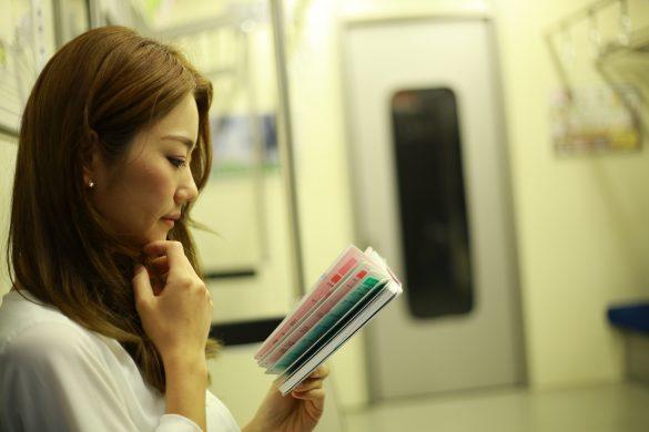 電車で本を読む女性