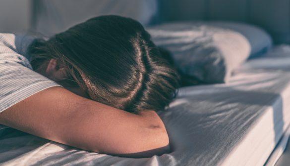 ベッドに突っ伏して泣く女性