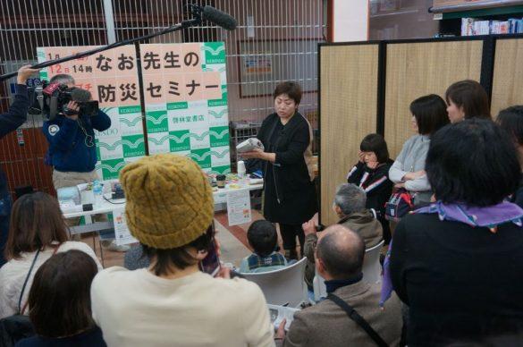 熱心に新聞足袋の作り方を見つめる参加者たち