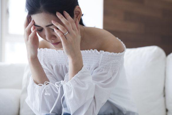 頭を抱える女性 悩む