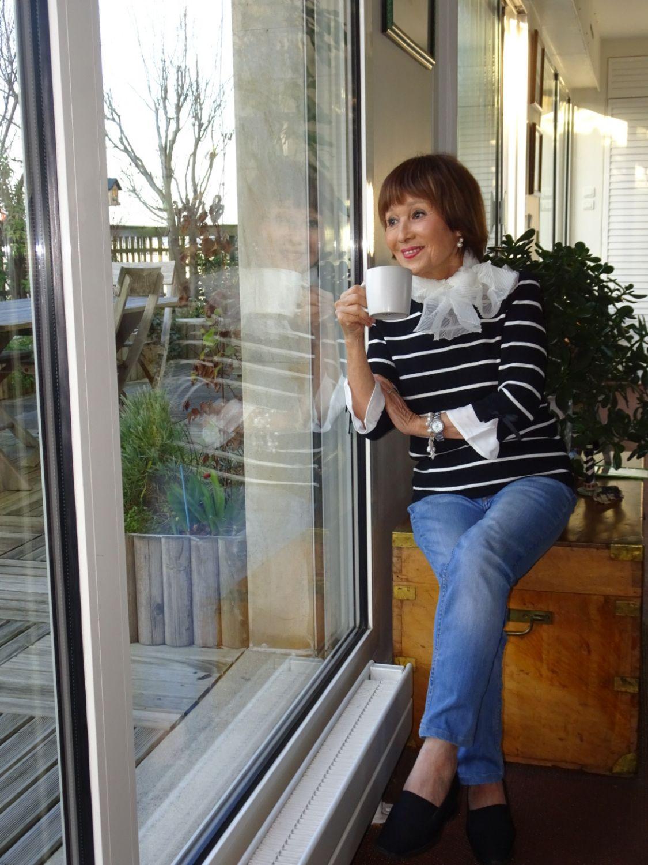 自宅リビングでテラスにつづく外の風景を眺めながらくつろぐ弓さん