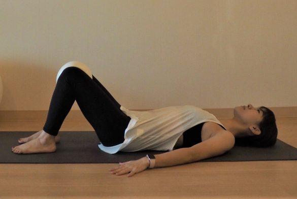 (1) 床に仰向けになりひざを立てたら、ひざとひざの間にクッションを挟む