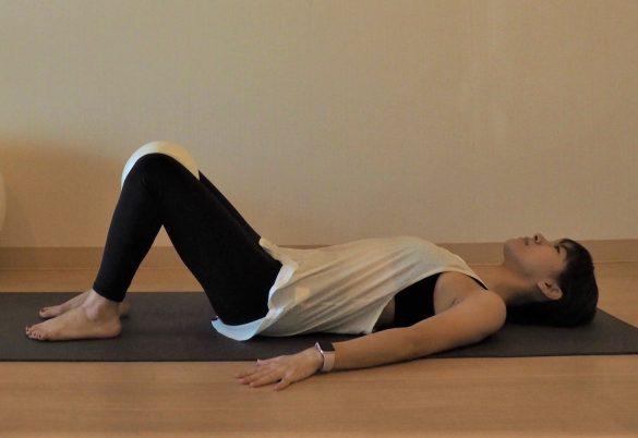 床に仰向けになりひざを立てたら、ひざとひざの間にクッションを挟む