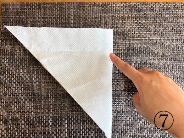 (7)もう一度逆三角形に開き、右端と左端の角が合うように半分に折る