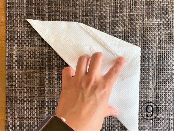 (9)その三角形の頂点部分に人差し指をあてながら、さらに大きく折る