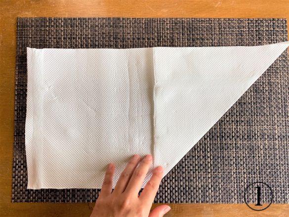 (1)キッチンペーパーを横長に置き、右下の角を中央に向けて折る
