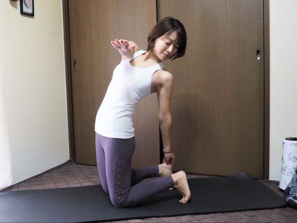 (3)(1)の姿勢に戻ったら、上体を左にねじり左手で右のかかとをつかむ~呼吸を5回繰り返す