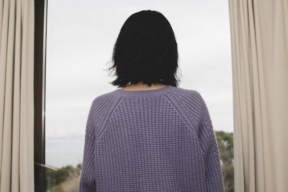 窓から外を眺める女性
