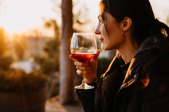 Young woman with a glass of red wine in sunset light at a terrace.