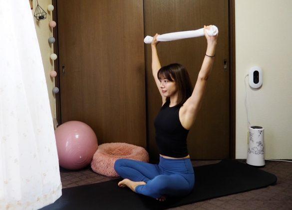 (1) 床や椅子に座り、タオルの両端を手で持ったら腕を頭上に伸ばす。